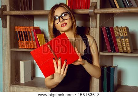 cute librarian reads a book with glasses in the library next to the bookshelf