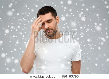 pain, stress, winter, christmas and people concept - young man suffering from headache over snow on gray background