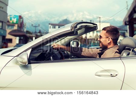 travel, tourism, transport, leisure and people concept - happy man driving cabriolet car over city in japan background
