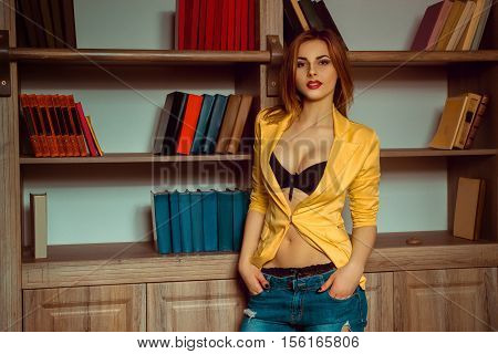 gorgeous girl in a yellow jacket unbuttoned posing against the backdrop of a bookcase