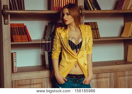 sexy girl in a yellow jacket unbuttoned posing against the backdrop of a bookcase