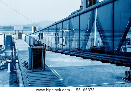 Shanghai Pudong Airport boarding bridge.Blue hue map.