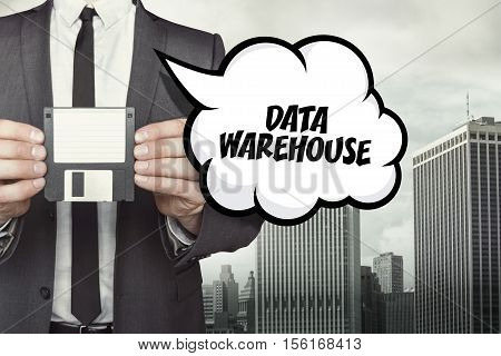 Data warehouse text on speech bubble with businessman holding diskette