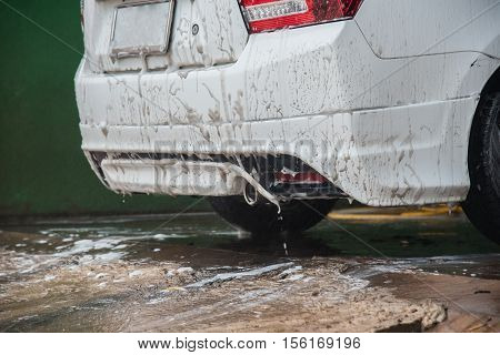Man washing his car and pulverizing water all over with a dynamic look suggesting car wash services on a premium auto vehicle in business car care