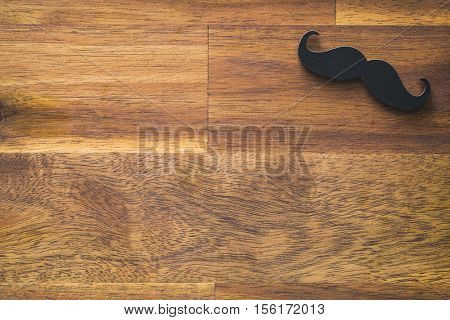 Fake black mustache on wooden background.