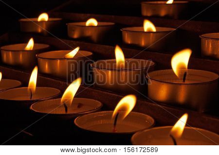 Group of votive candles (tea light) in a church on a dark background