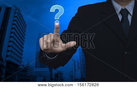 Businessman pressing question mark sign icon over city tower background Customer support concept