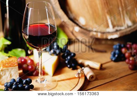 Wine glass, cheese, grapes and barrel on a table
