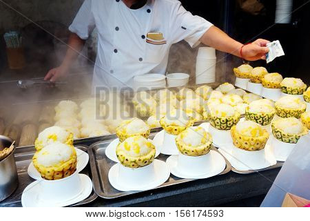 Chengdu snacks stall holders are selling delicious pineapple rice.