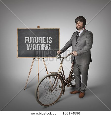 Future is waiting text on blackboard with businessman and vintage bike