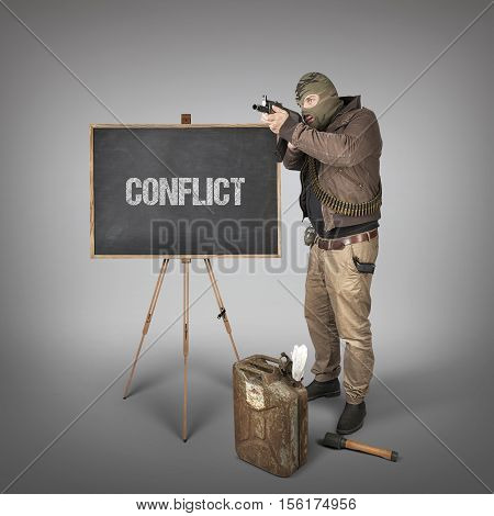 Conflict text on blackboard with terrorist holding machine gun