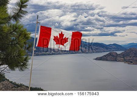 Canadian Flag flies over Okanagan Lake near Peachland British Columbia Canada on a windy day