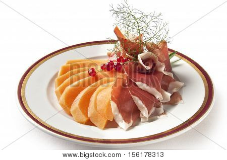 Appetizer dish of Parma ham and melon with currants isolated on withe