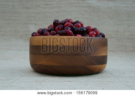 Fresh red and maroon cranberries heaped in turned wooden bowl. Photographed close up at eye level against an ecru background with shallow depth of field and fill flash.