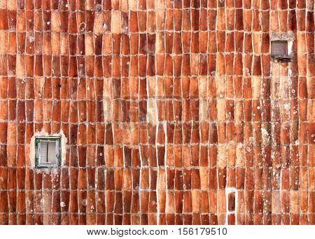 Wall decorated by roof tiles with two windows