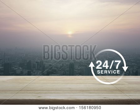 24 hours service icon on wooden table over aerial view of cityscape at sunset vintage style Full time service concept