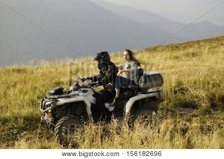 Handsome man and pretty girl ride quad bike on field road on mountain scene