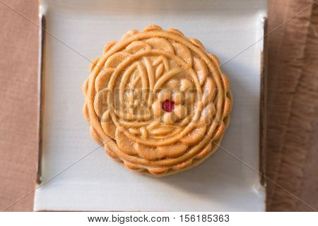 Moon cake - Chinese mid autumn festival moon cake on white plate with wooden board background. Closeup Select focus.