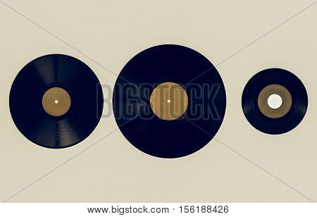 Vintage looking Size comparison of many analogue recording media for music. Left to right: shellac record 78 rpm vinyl record 33 rpm and 45 rpm - yellow label poster