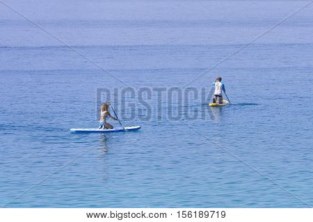 Man and woman facing away from the viewer paddling on surf boards; SUP suping