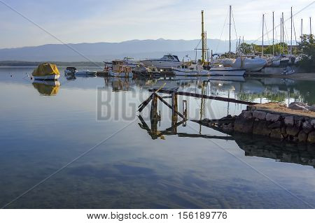 Traditional small town ship yard and marina in the morning a decayed rusty old pier in the foreground