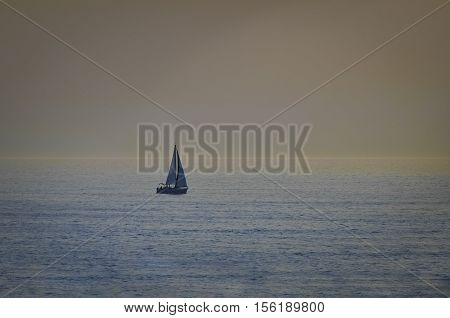 Sailboat in open sea at sunset calm seas no clouds