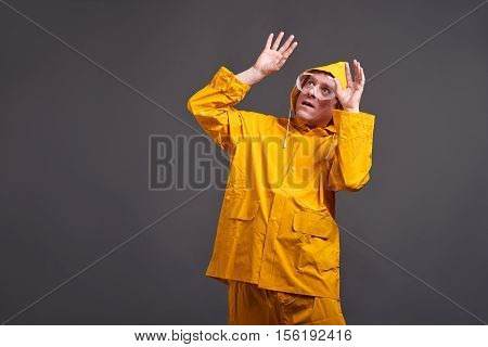 A middle aged man in a yellow raincoat and safety glasses feeling scared