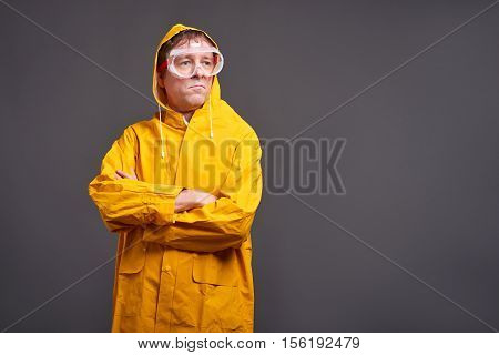 A serious middle aged man standing in a yellow raincoat