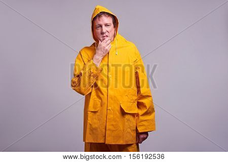 A middle aged man standing and thinking in a yellow raincoat