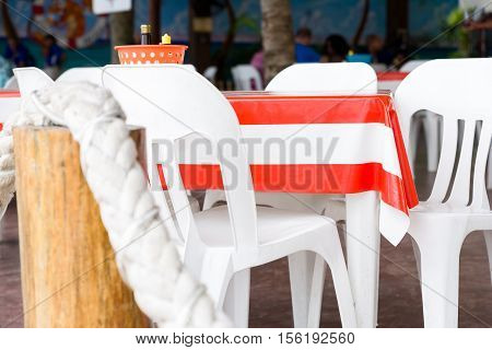 Outdoor cafe table draped with a orange striped vinyl tablecloth in Cozumel Mexico