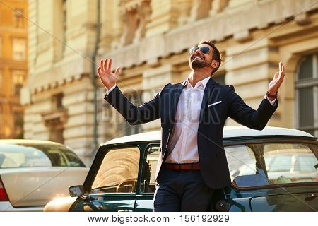 A handsome young businessman standing next to his car and celebrating