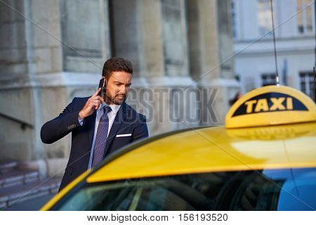 A handsome young businessman getting in to a taxi while talking on his phone