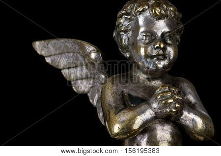 Praying winged putto side view on black background. Angel made of brass, covered with silver, part of a candelabra from nineteenth century. Symbol for religious passion. Macro object photo front view.
