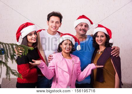 family, happiness, generation, holidays and people concept - happy indian family in santa helper hats standing and small girl presenting gesture at home, indian family and christmas