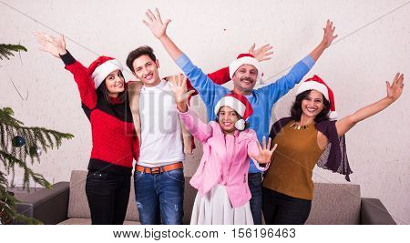 family, happiness, generation, holidays and people concept - happy indian family in santa helper hats dancing and stretching both hands with joy, happiness gesture, indian family and christmas