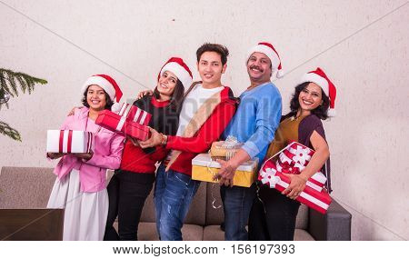 Happy indian family holding Christmas presents at home. merry Christmas