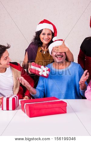 christmas time, Happy indian family sitting across table and exchanging christmas gifts wearing santa hat/cap, merry Christmas, indian family celebrating christmas