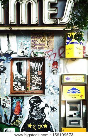 BERLIN, GERMANY - MAY 09: Graffiti and cartoon style street art next to an ATM money machine in Friedrichshain on May 09, 2016 in Berlin.
