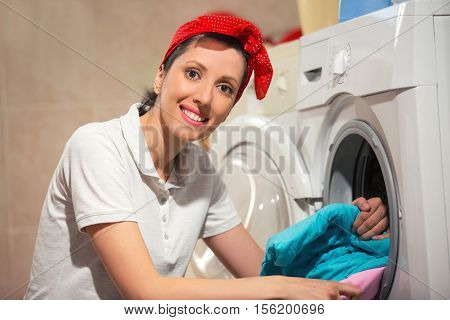 Young woman takes the laundry out of washing machine