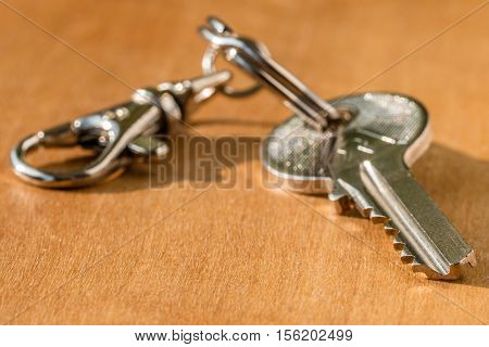 House key on a chain on a wooden background. Soft focus shallow DOF