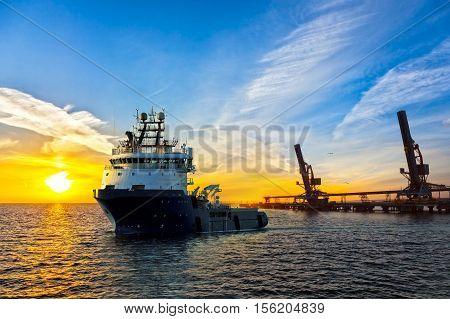 Big tugboat in a harbor at sunrise.