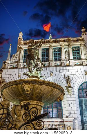 Neptune's fountain and Artus Court at night in Gdansk Poland.