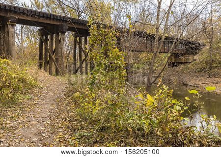 A railroad bridge crossing a river in the woods during autumn.