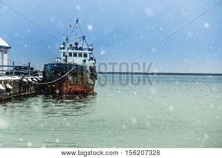 Boat Moor At Horbor In Snow Strom Day.
