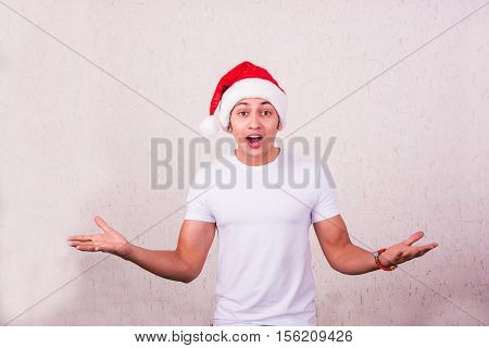 Young smiling indian man with santa hat in the presentation pose, on white background, indian man showing christmas offers or surprised with both hands stretched open