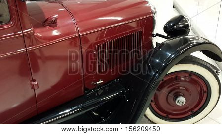 Gdansk, Poland - November 12, 2016: Red and black Studebaker Big Six, front right tire, bumper and lamp