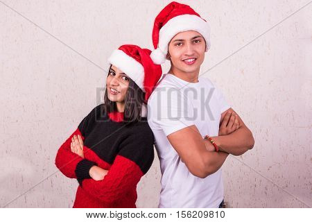 Young indian couple is standing back to back with hands folded on christmas eve with santa hat on head, both looking over shoulder, isolated on white background