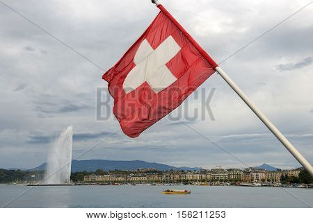 swiss flag on the background of lake Geneva with the Jet d'eau fountain and the promenade of Mont-Blanc in Geneva, Switzerland
