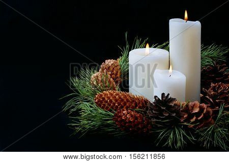 Dark times of the year. Winter decoration with pine branches wreath and burning candles.