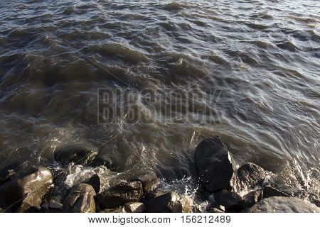 Lumpy Caspian Sea on Sunset. Waves and Rocks